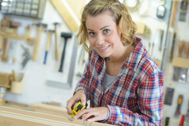Woman measuring wooden board with tape measure stock photo
