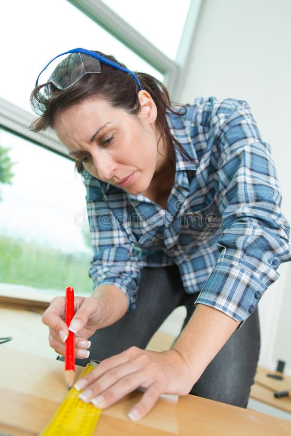 Woman measuring wooden board with tape measure stock images