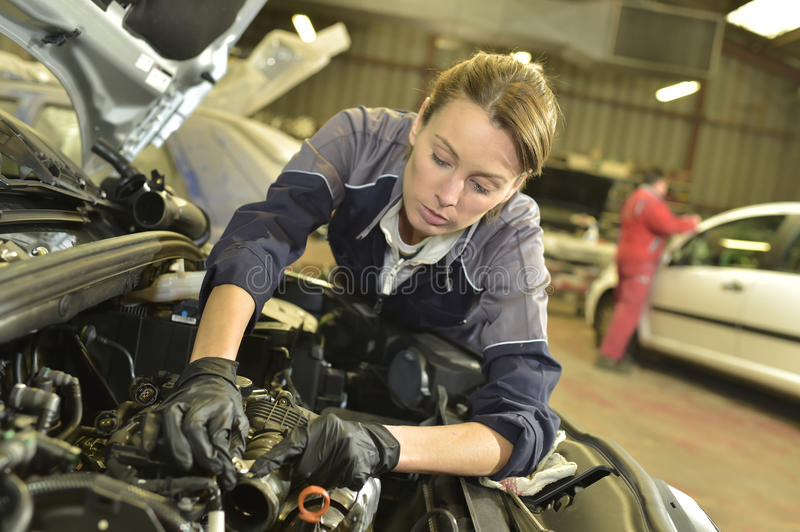 Woman mechanic doing car reparations royalty free stock images