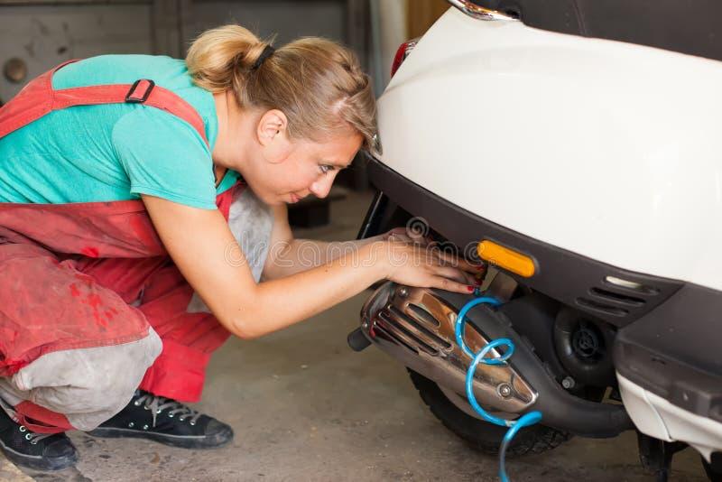 Woman mechanic pumping a tire on a motor bike royalty free stock photo