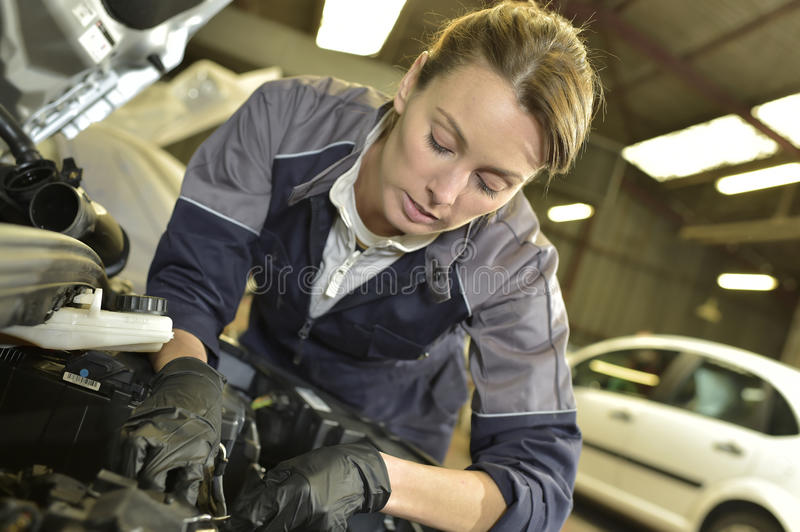 Woman mechanic repairing the car stock photography