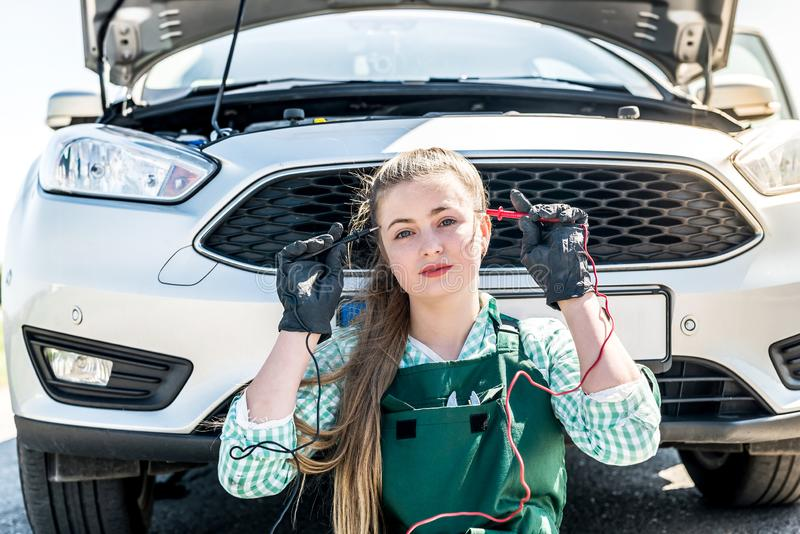 Woman mechanic searching problems with car engine stock photography