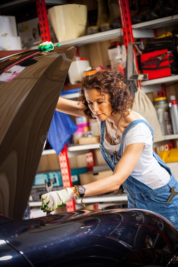 Woman mechanic with a wrench adjusts the car`s engine stock photos