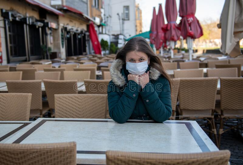 Woman with medical mask in empty cafe terrace royalty free stock photo