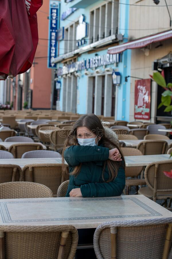 Woman with medical mask in empty cafe terrace royalty free stock photos