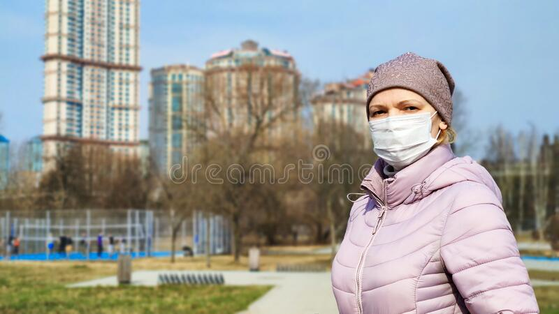 Woman with medical mask on face in city park during COVID-19 coronavirus outbreak stock images