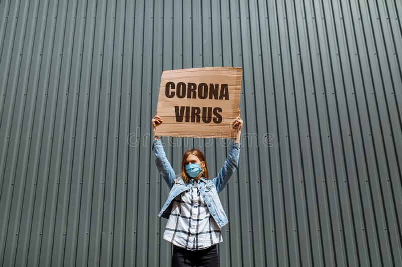 Woman in a medical protective mask holds a cardboard poster with the words coronavirus, standing in the city against a gray wall. A young woman in a medical royalty free stock photo