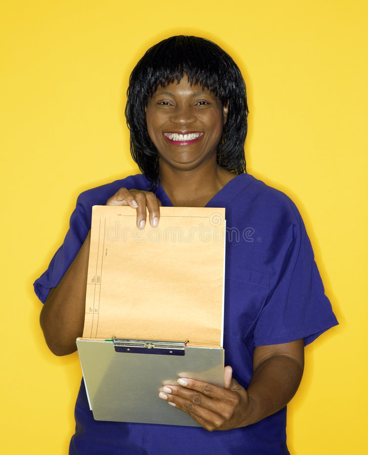 Woman in medical uniform. African-American mid-adult woman in medical uniform smiling reading chart stock photo