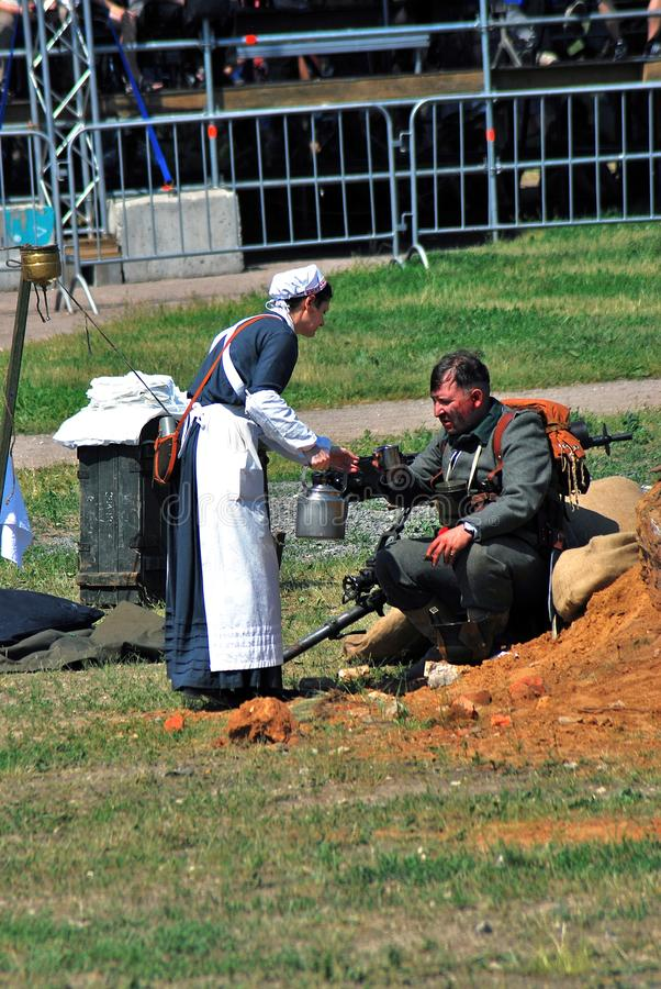 Woman in medical uniform brings water to a man. MOSCOW - JUNE 08, 2014: Woman in medical uniform brings water to a man. She wears a white apron and hat stock photo