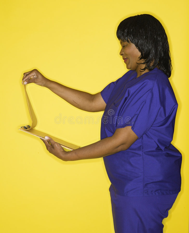 Woman in medical uniform reading chart. African-American mid-adult woman in medical uniform smiling reading chart royalty free stock images