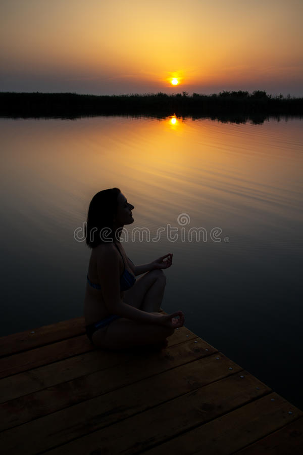 Woman meditate in sunset on the wooden dock. stock image