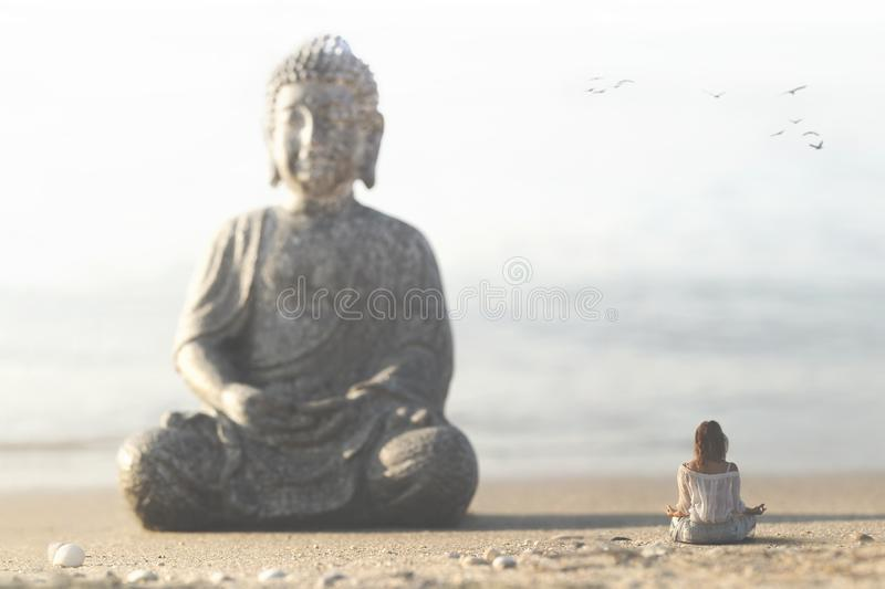 Woman meditates in front of the buddha statue in the middle of nature stock image