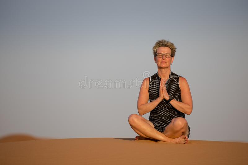 Mindfulness. A woman meditates in sand dunes during sunset. royalty free stock photo