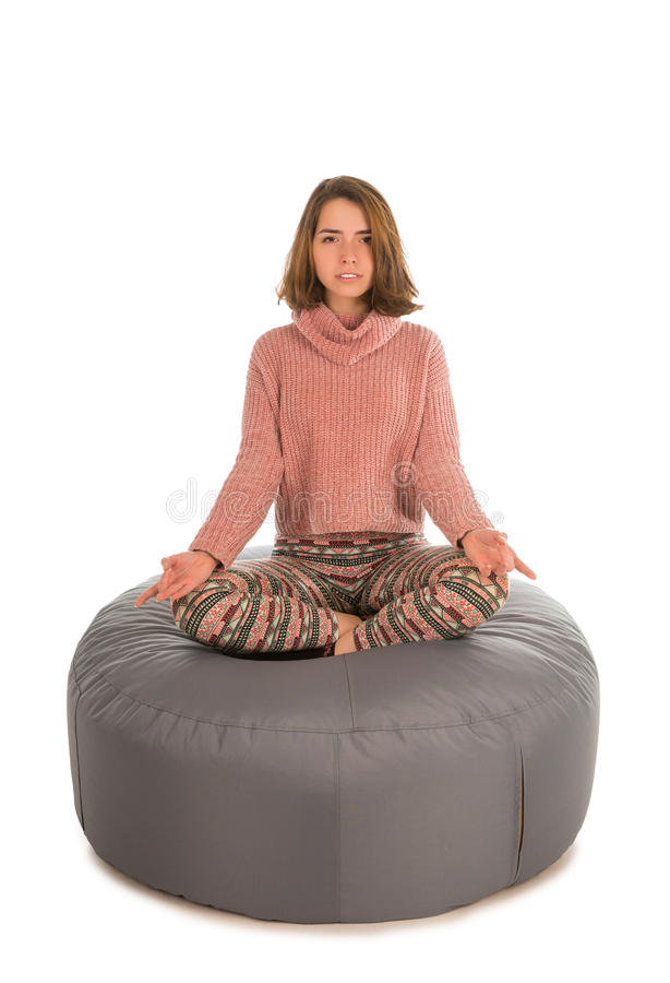 Woman meditates while sitting in the lotus position on round shape grey beanbag chair. On white background stock images