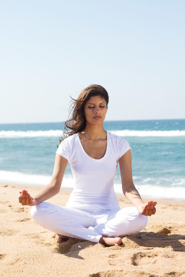 Woman meditating on beach royalty free stock images