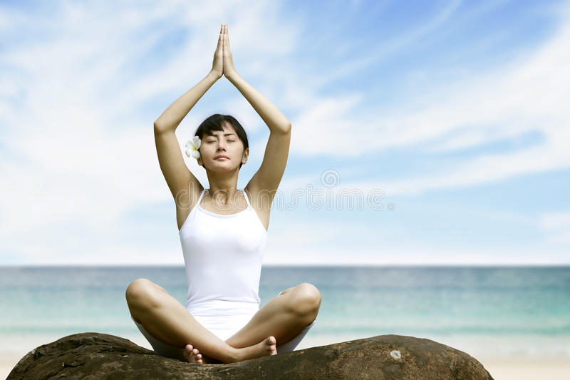 Woman meditating at beach royalty free stock images