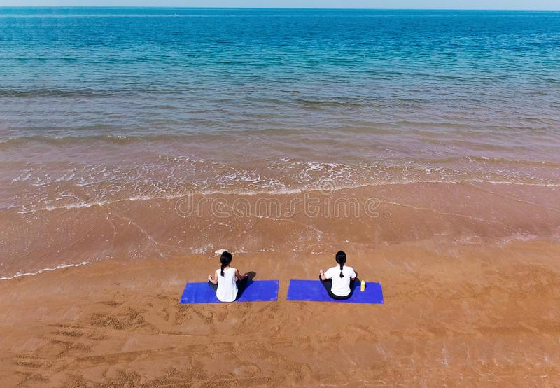 Woman meditating on the beach aerial. View women yoga meditate mat above drone relaxation seaside two friends fitness together girlfriends summer sit sitting royalty free stock photos