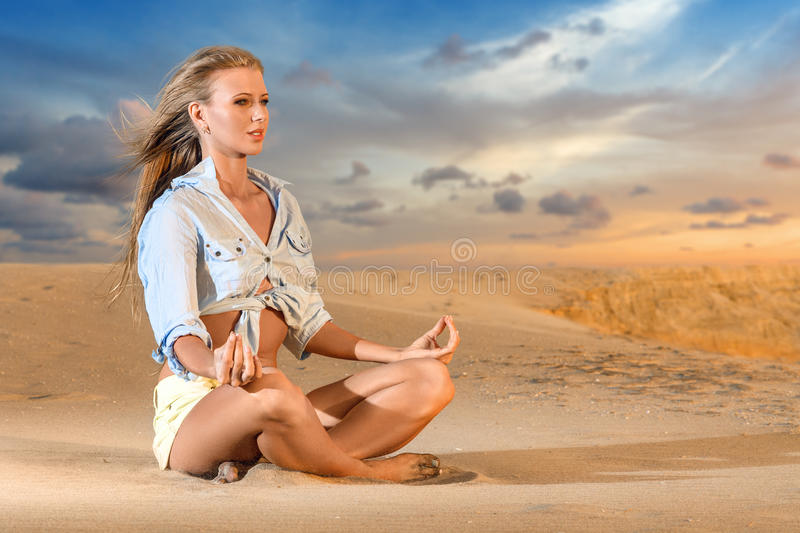 Woman meditating on the beach royalty free stock image