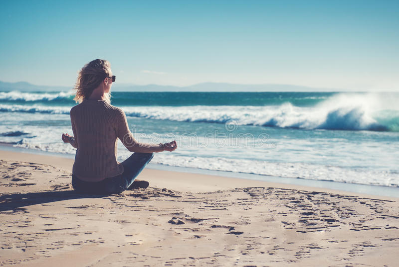Woman meditating on the beach. Young woman meditating on the beach royalty free stock photos