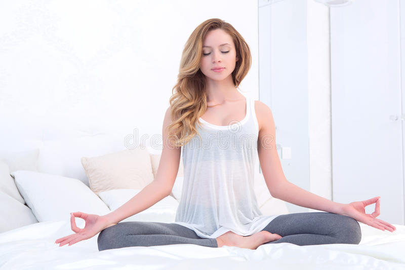 Woman meditating in bedroom royalty free stock image