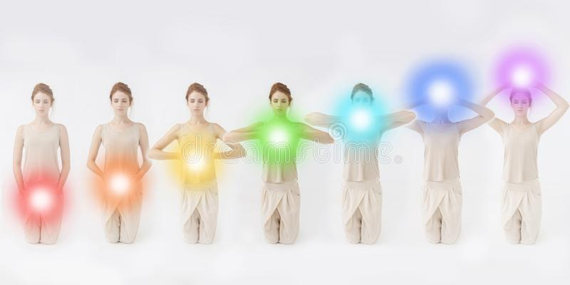 Seven Chakras concept. Woman meditating. Colored chakra lights over her body. Yoga, zen, Buddhism, recovery and wellbeing concept royalty free stock images