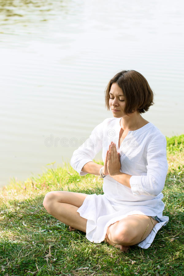 Woman meditating in easy pose on the grass at the river-bank. royalty free stock images