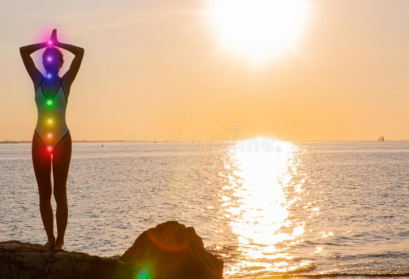 Woman is meditating with glowing seven chakras on the beach. Silhouette of woman is practicing yoga at sunset. On sea shore. Kundalini meditation royalty free stock image