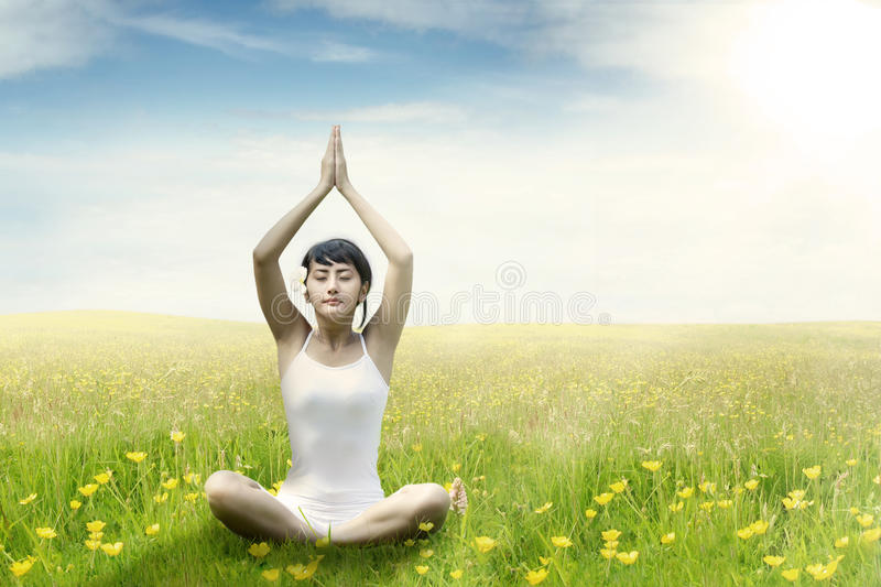 Woman meditating on grass at field stock image