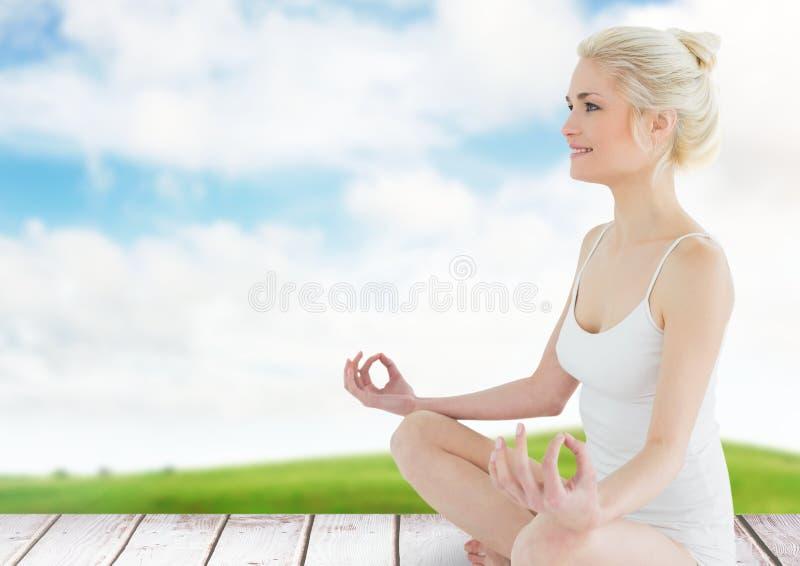 Woman Meditating by green field. Digital composite of Woman Meditating by green field stock photography