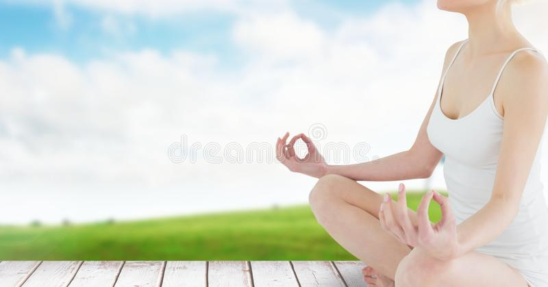 Woman Meditating by green field and sky. Digital composite of Woman Meditating by green field and sky royalty free stock photography
