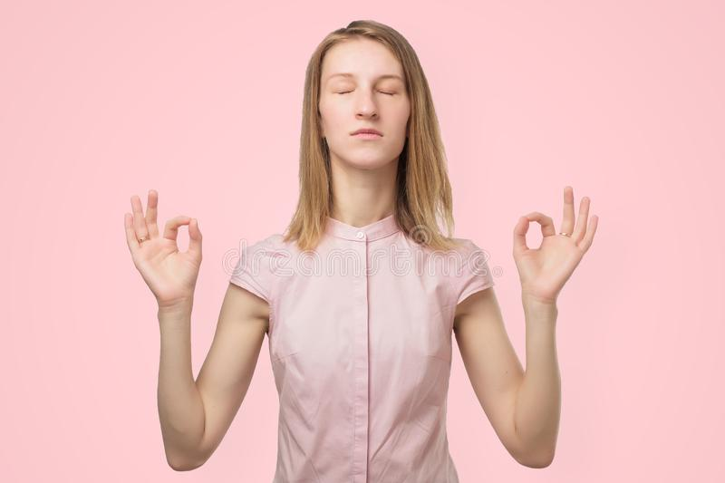Woman meditating, holding her hands in yoga gesture, feeling calm and positive stock photography