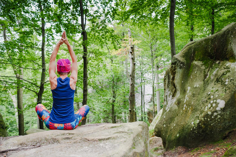 Woman meditating in lotus pose, doing yoga on a rock. In the forest royalty free stock photography