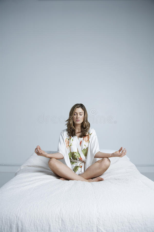 Woman Meditating In Lotus Position On Bed. Full length of young woman meditating in lotus position on bed royalty free stock photography