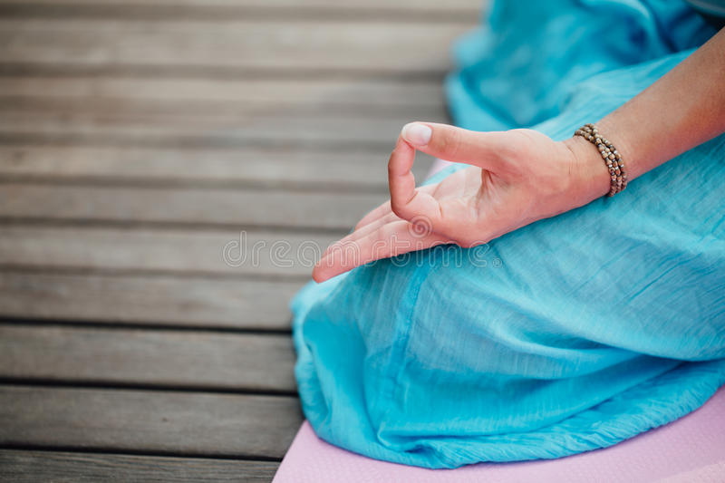 Woman meditating in the lotus position closeup. Hands close-up. stock photography