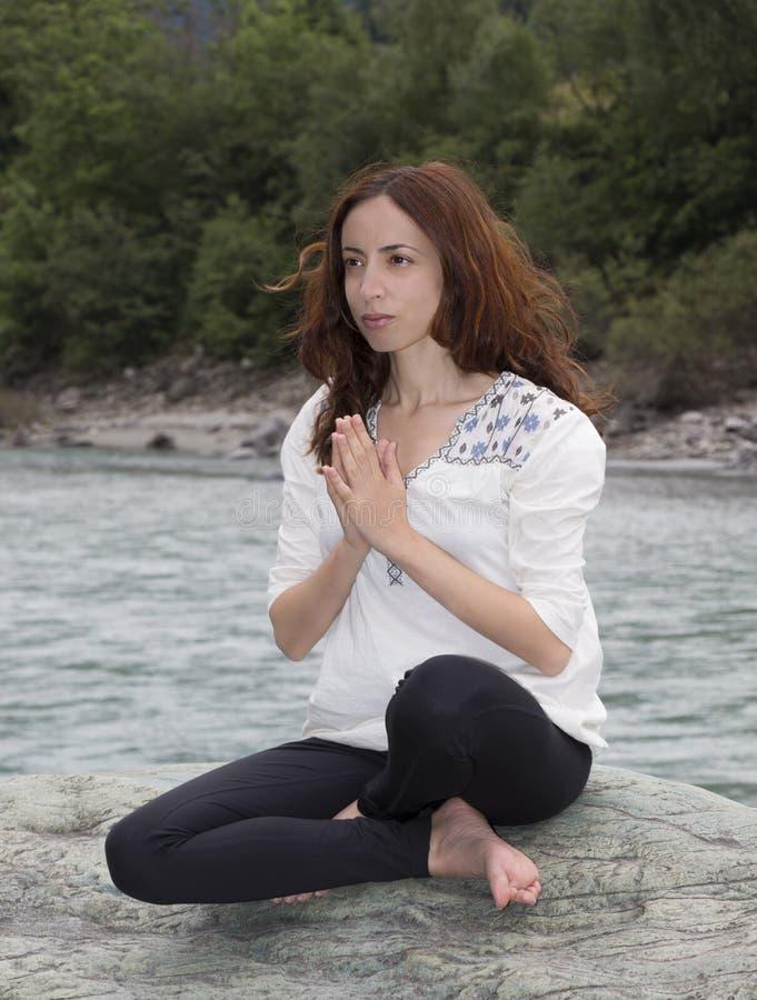 Woman meditating outdoors stock photography