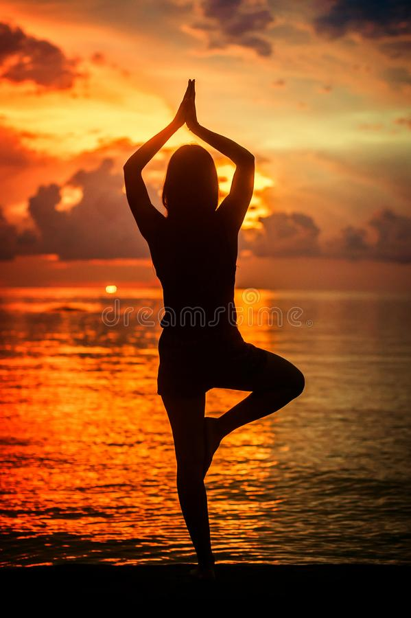 Woman meditating, relaxing in yoga pose at sunset, zen meditation. Silhouette in lotus pose. Mind body spirit concept stock photo
