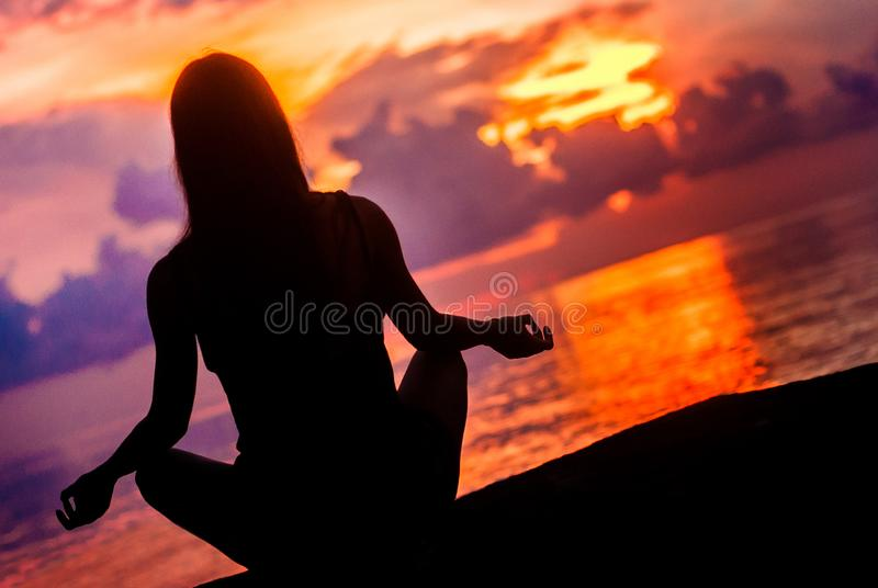 Woman meditating, relaxing in yoga pose at sunset, zen meditation. Silhouette in lotus pose. Mind body spirit concept stock photography