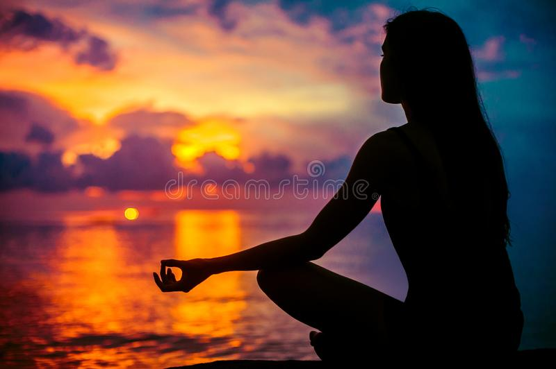 Woman meditating, relaxing in yoga pose at sunset, zen meditation. Silhouette in lotus pose. Mind body spirit concept royalty free stock photos