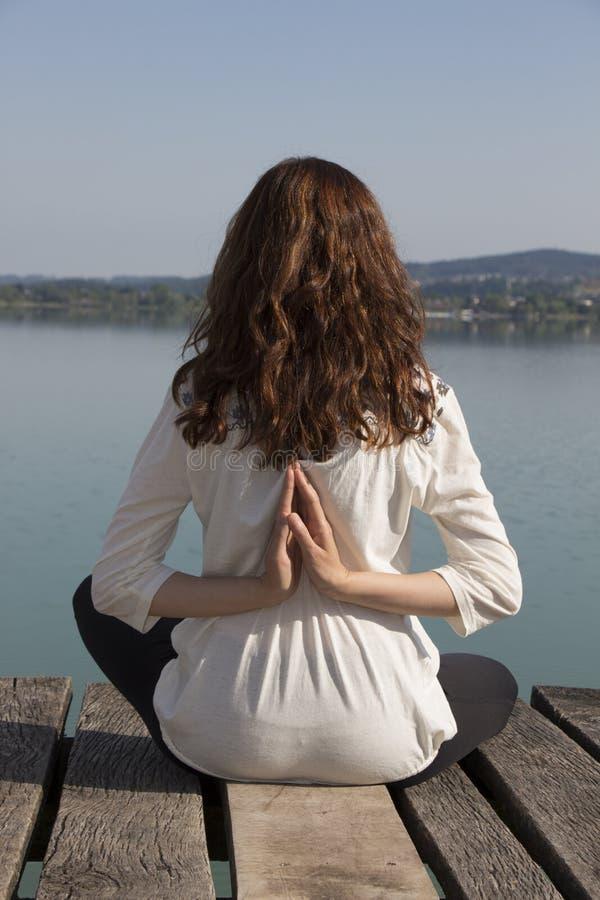 Woman meditating in reverse namaste pose during yoga by lake royalty free stock photo