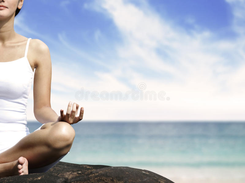 Woman meditating on a rock stock image