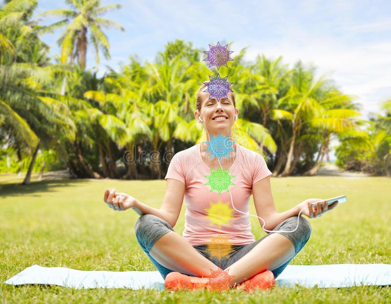 Woman meditating in summer park with seven chakras royalty free stock images