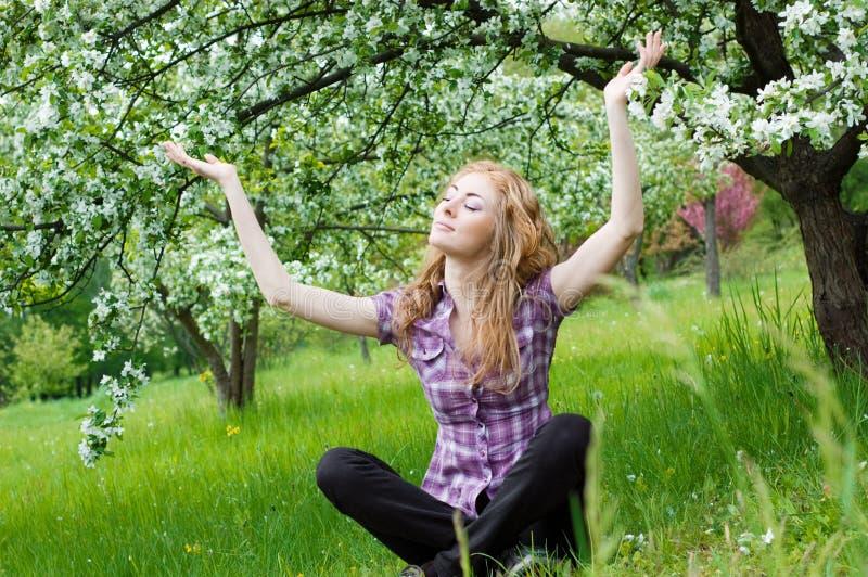 Woman Meditating Under Blooming Tree Royalty Free Stock Image