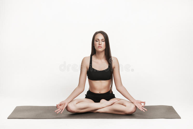 Woman meditating on yoga mat stock images