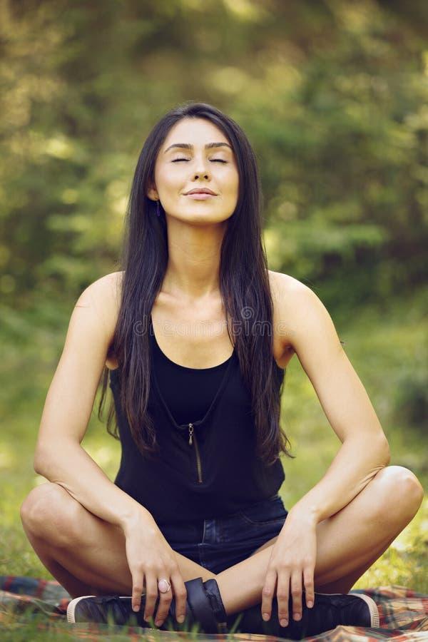 Woman meditating in yoga position. Beautiful young woman meditating in yoga position royalty free stock photo