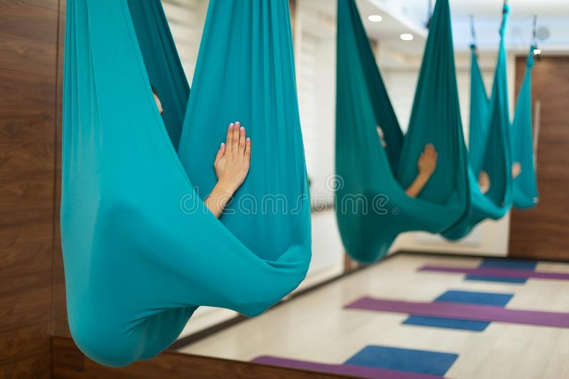 Woman meditation in hammock. fly yoga stretching exercises in gym. Fit and wellness lifestyle.  royalty free stock photo