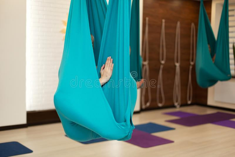 Woman meditation in hammock. fly yoga stretching exercises in gym. Fit and wellness lifestyle.  stock image