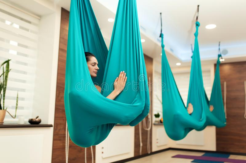 Woman meditation in hammock. fly yoga stretching exercises in gym. Fit and wellness lifestyle royalty free stock photo