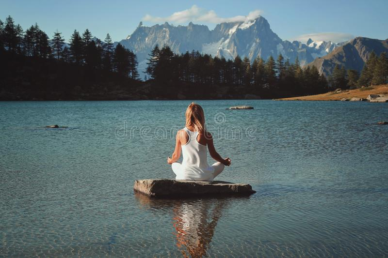Woman meditation in mountain lake royalty free stock photography