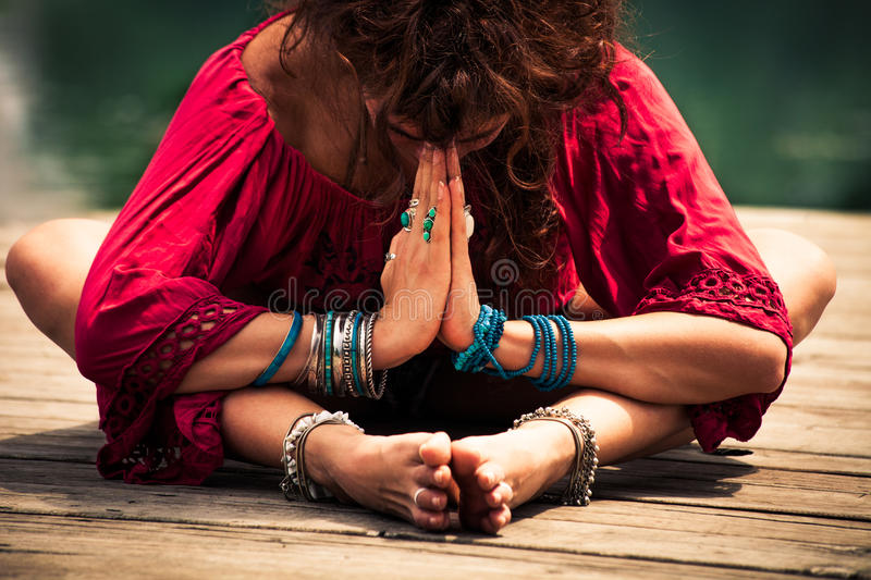 Woman in a meditative yoga position closeup stock photos