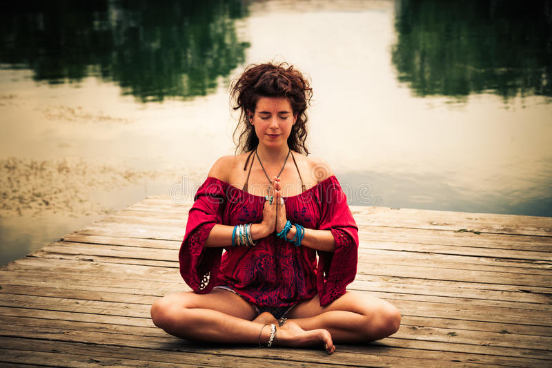 Woman in a meditative yoga position by the lake stock images